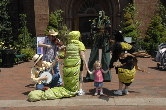 Bluegrass musicians, giant insects and stilt walker Tim Marrone entertained visitors, including tiny Lindsay Brown (center), at last year's Garden Fest. (Photo by Harold Dorwin)
