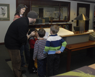 """Leslie Overstreet and Joshua Beasley (in cap) help young students explore the beauties of Jonathan Singer's """"Botanica Magnifica."""" (Photo by Liz O'Brien)"""