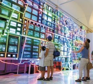 """Visitors to the American Art Museum marvel at """"Electronic Superhighway: Continental U.S., Alaska, Hawaii"""" by Nam June Paik. (Photo by Ken Rahaim)"""