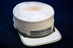 """This hat was worn by a sleeping car porter who worked on the midwestern Chicago, Milwaukee, & St. Paul Railroad. White hats were worn by the more experienced porters when they serviced private cars for prominent guests. The hat was donated to the Museum of African American History and Culture during a """"Save Our African American Treasures"""" program at the Chicago Public Library."""