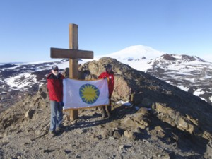 Kristina Johnson and Wayne Clough hoist the Smithsonian flag atop Observation Point. Mount Erebus can be seen in the background.