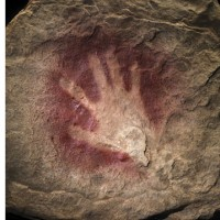 This 30,000-year-old handprint from Chauvet Cave in France, made by mixing pigment with saliva inside the mouth and blowing the mixture onto a cave wall, is an emblem of the deep history of human creativity. (Photo by James DiLoreto and Donald Hurlbert)