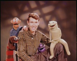 """Jim Henson poses with characters from the TV show """"Sam and Friends,"""" ca. 1956/57. Left to right: Harry the Hipster, Sam, Jim Henson, Kermit (original), Yorick. (Photo courtesy The Jim Henson Company and The Muppets Studio LLC)"""
