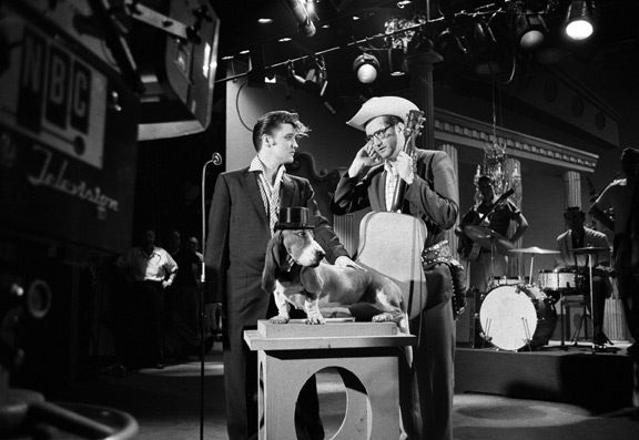 "Elvis, Steve Allen and The Basset Hound. Steve Allen, and Elvis discuss in rehearsal how Elvis will sing his song, ""Hound Dog,"" to a basset hound on a pedestal wearing a top hat. Allen wanted to avoid the controversy that occurred after Elvis swiveled his hips on ""The Milton Berle Show."" NBC Television, Hudson Theater, New York City. July 1, 1956. © Alfred Wertheimer. All rights reserved."