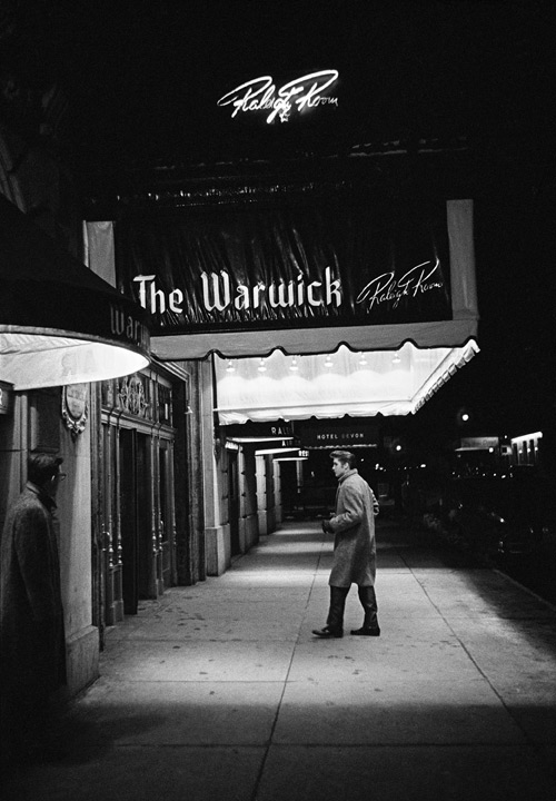 "Entering The Warwick. Between the afternoon rehearsal and the evening performance of ""Stage Show,"" hosted by Tommy and Jimmy Dorsey, Elvis returns to his hotel to rest and freshen up. New York City. March, 17, 1956. © Alfred Wertheimer. All rights reserved."