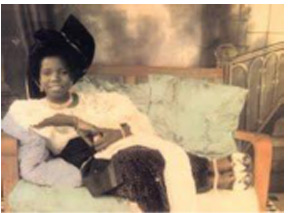 Reclining woman, c. 1940. Photograph by Chief Solomon Osagie Alonge. Hand colored print from glass plate negative.