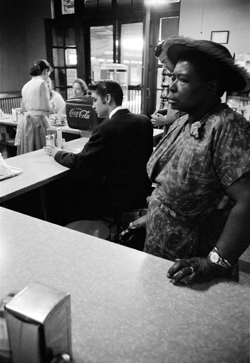 Segregated Lunch Counter. While waiting for a train to take him from Chattanooga to Memphis, a trip of some 400 miles, Elvis sits at the lunch counter to have some breakfast. The woman standing had ordered a sandwich for which she was waiting, but was not able to sit at the counter. Railroad station, Chattanooga, Tenn. July 4, 1956.© Alfred Wertheimer. All rights reserved.