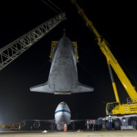 The space shuttle Discovery is suspended from a sling held by two cranes shortly after the NASA 747 Shuttle Carrier Aircraft (SCA) was pushed back from underneath at Washington Dulles International Airport, Thursday, April 19, 2012, in Sterling, Va.