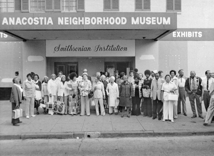Large group of people posed in front of building with The Neighborhood Museum Sign