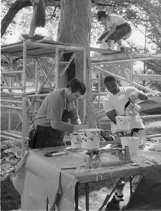 Office of Exhibits Central Modelmakers Paul Rymer, top left, and Carolyn Thome, top right, work on a mold to be cast into a beehive for the new Orkin Insect Zoo as Natural History Exhibits staffers Robert Gibson, left, and Anthony Bowden mix up the resin. (Photo by Laurie Minor-Penland, as featured in the Torch, November 1992)