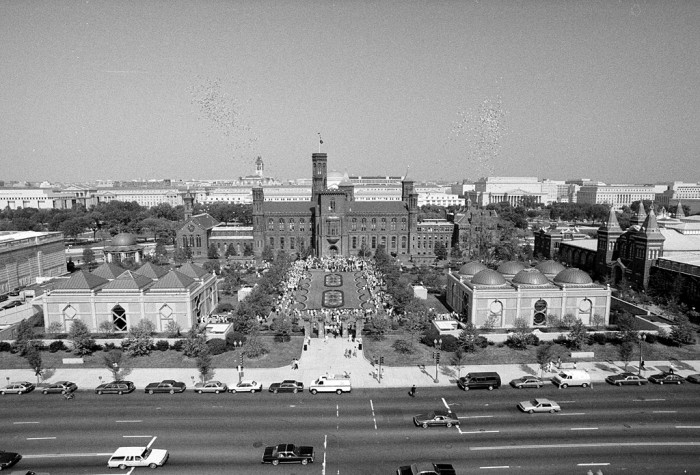 Ribbon cutting ceremony for the inauguration of the Smithsonian Institution's two new museums: The Arthur M. Sackler Gallery on the left with pyramided roof, and the National Museum of African Art with domed roof on the right. Hundreds of people crowded the Enid A. Haupt Garden which sits atop the underground museums. This photo was at about 12:25 p.m. as 2,500 blue and yellow balloons filled the sky over the National Mall in Washington, D.C., September 28, 1987. (Photo by Jeff Tinsley)
