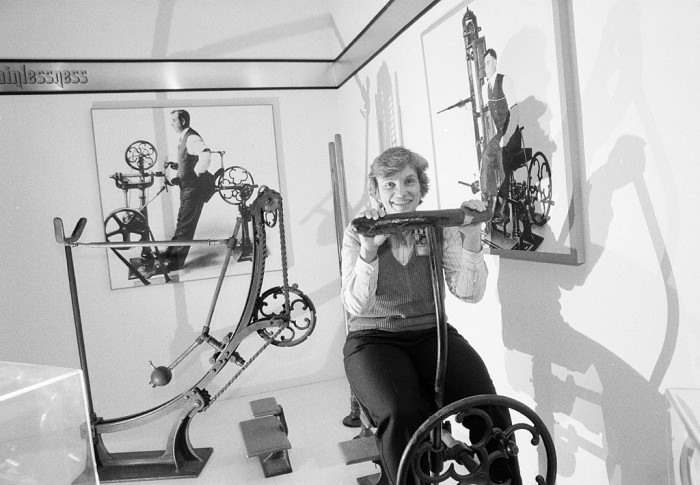 """Medical sciences curator Audrey Davis poses on a turn-of-the-century Zander exercise machine in the exhibit """"Pain and Its Relief"""" on the National Museum of American History's first floor. (Photo by Jeff Tinsley, as featured in the Torch, June 1989)"""