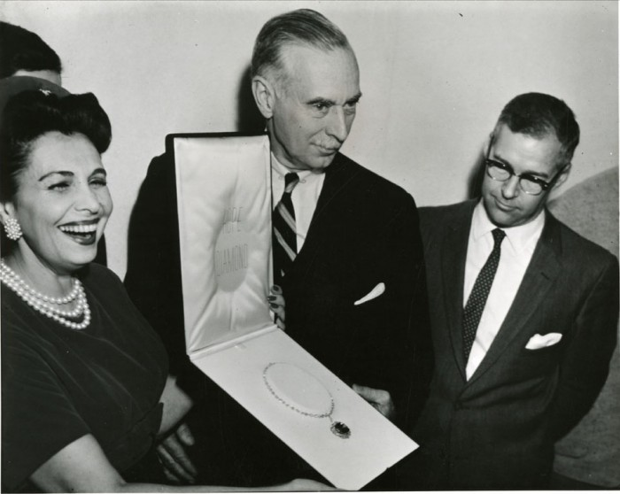 A woman and two men holding jewel case with necklace.