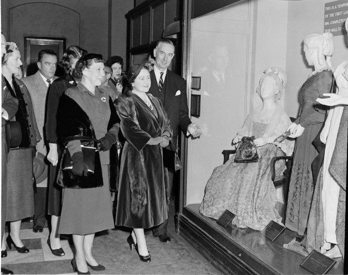 First Lady Mrs. Dwight D. (Mamie) Eisenhower (left), the Queen Mother, Lady Elizabeth Bowes-Lyon (center), and Secretary Leonard Carmichael looking at a case of the First Ladies Gowns in the Arts and Industries Building, November 5, 1954.