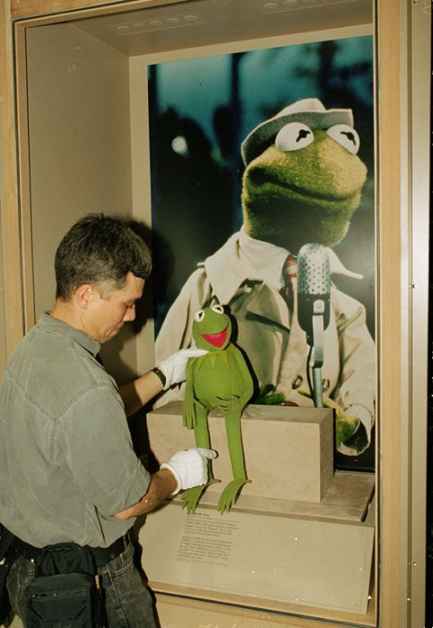 """""""Kermit the Frog"""" is placed in his display case as part of the """"America's Smithsonian"""" exhibition at the Los Angeles Convention Center that opened Feb. 9, 1996. (Photo by Hugh Talman)"""