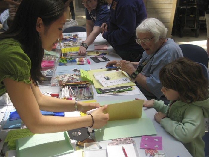 A volunteer shows a child how to make a storybook letter at an Asian Pacific American Heritage Month program at the National Postal Museum.