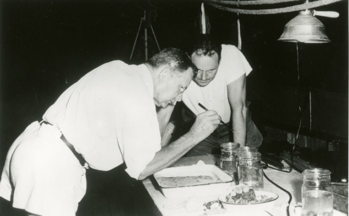 """On board the ship """"Freelance"""", J. F. Gates (John Frederick Gates) Clarke, 1905-1990, left, and Waldo LaSalle Schmitt, 1887-1977, right, part of the Smithsonian-Bredin Caribbean Expedition of 1956, examine specimens they collected. . F. Gates (John Frederick Gates) Clarke, 1954-1963, was curator of Lepidoptera and Waldo LaSalle Schmitt, 1957-1977, was curator of Invertebrate Zoology, at the National Museum of National History"""