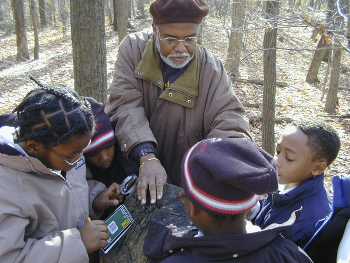 Fifth graders from Our Lady of Perpetual Help School, Washington, DC, walk the Dr. George Washington  Carver Nature Trail at the Anacostia Community Museum with Dr. Jawara Kasimu-Graham. He shows them how to use a magnifying glass to count