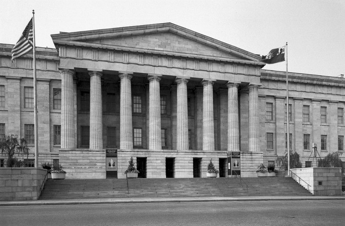 The National Collection of Fine Arts, now known as the Smithsonian American Art Museum, is located on this side of the Old Patent Office Building at 8th and G Streets, N.W. The National Portrait Gallery is located on the opposite side (not shown in photograph). The Old Patent Office building is a Greek Revival structure, built (1836-66) by Robert Mills and became home to the National Collection of Fine Arts in 1968. In 1980, NCFA was renamed the National Museum of American Art, and then in 2000 it became known as the Smithsonian American Art Museum. (Photographer unknown, via Smithsonian Institution Archives)