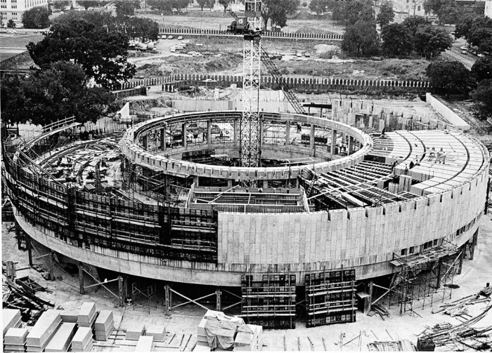 Aerial view of the Hirshhorn Museum and Sculpture Garden under construction, 15 August 1972. The museum building is at about half its height, with the outer wall only half complete. There is a crane in the center of the building, and the sculpture garden can be seen in the background. (Photographer unknown, as featured in the Torch, October 1984)
