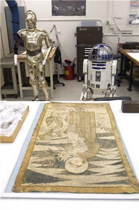 "Items from the ""Treasures of American History"" are put on display as they are being prepared for their new exhibit. C-3PO and R2-D2, droids from the movie Star Wars, are in the center and a tapestry lies on the table. The exhibit includes iconic items from the National Museum of American History (NMAH) that will travel across the National Mall to the National Air and Space Museum while NMAH is undergoing renovations starting September 5, 2006"