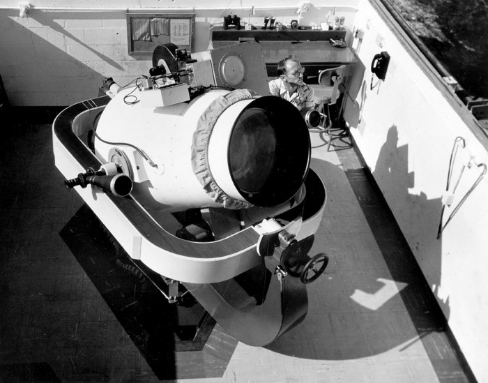 Looking down on the Baker-Nunn Camera, ca. 1958, one of the world's most sensitive devices for observing artificial satellites. A network of twelve tracking stations equipped with such cameras is maintained by the Smithsonian Astrophysical Observatory for the observation of both natural and artificial objects in space. The stations are located in Argentina, Australia, Curacao, India, Iran, Japan, Peru, South Africa, Spain, and at three sites in the United States