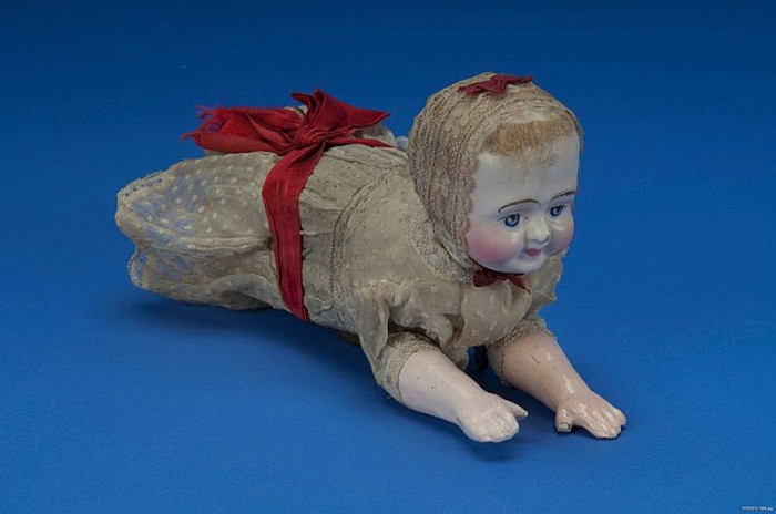 This doll, made c. 1900, was an improvement on Clarke's design. Inside the doll's body is a spring-driven brass mechanical movement that actuates the arms and legs in imitation of crawling, though the doll actually moves along on two concealed wheels.