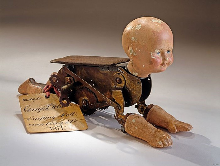 This patent model accompanied George Pemberton Clarke's patent submission for a moving baby doll. The doll's head, two arms, and two legs are made of plaster. The arms and legs are hinged to a brass clockwork body that imitates crawling by rolling along on two toothed wheels.