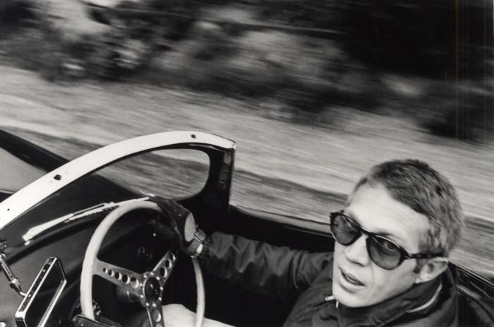 Steve McQueen in sunglasses driving a convertible