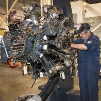 Collections specialist Scott Wood examines the engine of the Curtiss SB2C-5 Helldiver, the first aircraft to be restored in the Mary Baker Engen Restoration Hangar at the Steven F. Udvar-Hazy Center in Chantilly, VA. Collections specialists began work in early 2013 by examining, documenting, and cleaning sections of the aircraft prior to restoration. (Photo by Dale Penland)