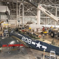 On March 4, 2014, the Curtiss SB2C-5 Helldiver's engine is lifted by crane into place. (Photo by Dane Penland)