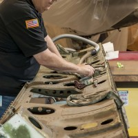 Museum specialist Carl Schuettler does initial cleaning of one of the Helldiver's two bomb bay doors. (Photo by Dane Penland)