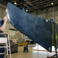 Museum specialist David Wilson prepares the tail horizontal section for painting. (Photo by Dane Penland)