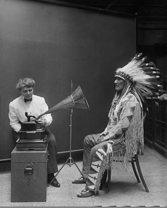 "Part of a series of pictures depicting Frances Densmore at the Smithsonian Institution in 1916 during a recording session with Blackfoot chief Mountain Chief for the Bureau of American Ethnology. Library of Congress caption: ""Piegan Indian, Mountain Chief, listening to recording with ethnologist Frances Densmore, 2/9/1916."" National Geographic caption: ""This 1916 image of Frances Densmore and Blackfoot leader Mountain Chief listening to a cylinder recording has become a symbol of the early songcatcher era."""