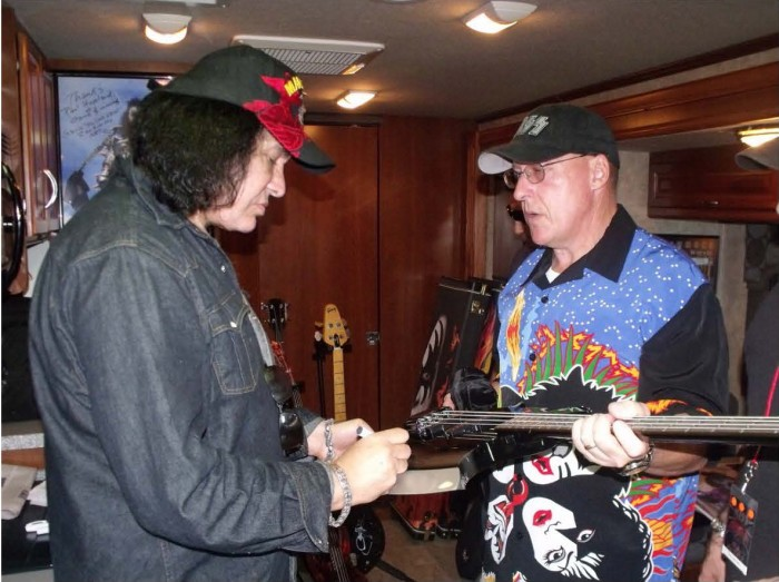 Gene Simmons autographs a guitar for John Downs
