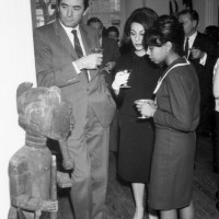 Actor Gregory Peck, Veronique Peck, and an unidentified woman admire African art at the Museum of African Art