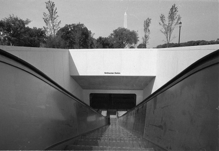 The Smithsonian Metro Station, looking down the escalators to the entrance of the terminal. The station was opened July 4, 1977. The Washington Monument is visible in the background