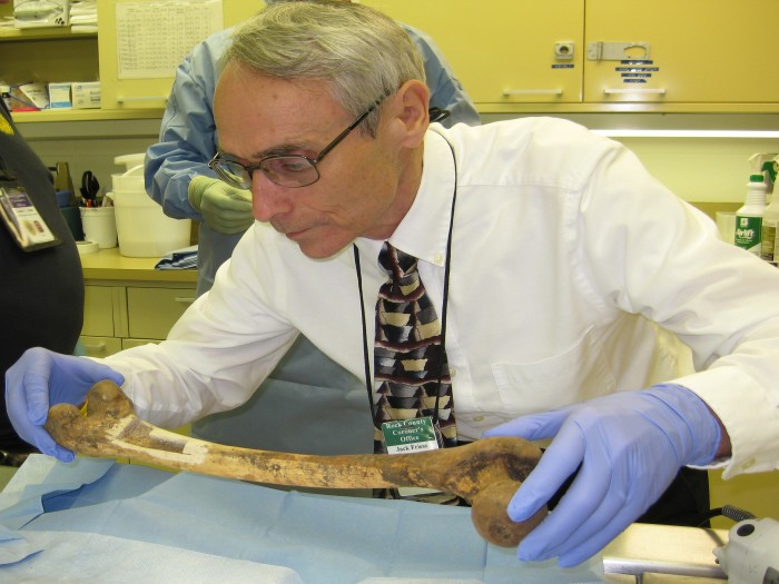 ack Friess, Rock County Deputy Coroner, inspects a femur at the Rock County Coroner's Office from which samples were taken and sent to the Smithsonian's Museum Conservation Institute for analysis. (Image courtesy Rock County Coroner's Office)