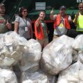 Sustainability team gives thumbs up in front of trash truck and bags of trash.
