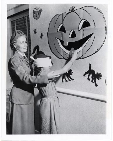 Blindfolded child pinning a doughnut to a jack-o'-lantern's mouth, ca. 1930-1940. Sally L. Steinberg Collection of Doughnut Ephemera, Archives Center, National Museum of American History.