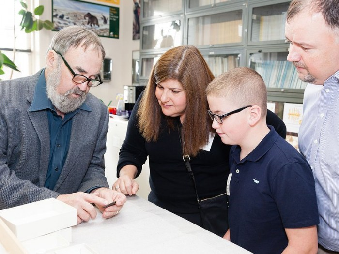 Ten-year-old Noah Cordle visited the National Museum of Natural History on November 3 to donate a Clovis point he found in New Jersey. He and his parents (right) met with the museum's Dennis Stanford (left). (Photo by Donald E. Hurlbert)