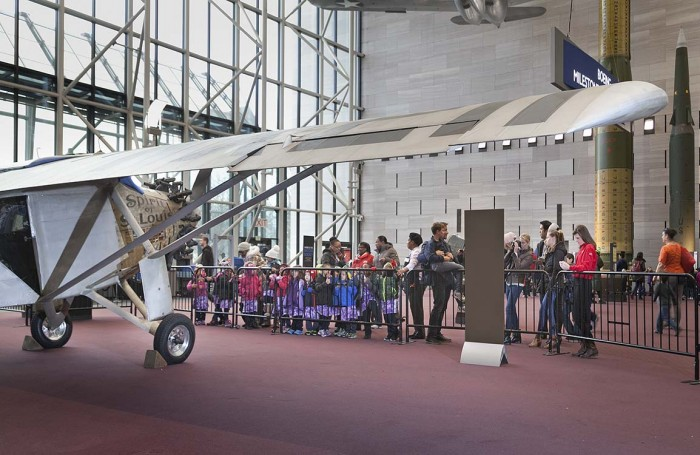 """Children from Shepard Elementary School in Washington, D.C., and other visitors to the National Air and Space Museum, get an up-close look at the look at the """"Spirit of St. Louis"""" on the floor of the Milestones of Flght Gallery. (Photo by Eric Long)"""