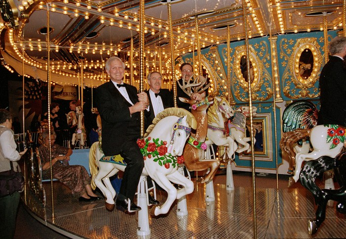 """From left, Smithsonian Secretary I. Michael Heyman, Provost Dennis O'Connor and curator Marc Pachter ride a carousel set up at the Los Angles Convention Center, first stop of the """"America's Smithsonian"""" national tour celebrating the Smithsonian's 150th anniversary. The exhibition opened in Los Angeles Feb. 9, 1996. (Photographer unknown, via Smithsonian Institution Archives)"""