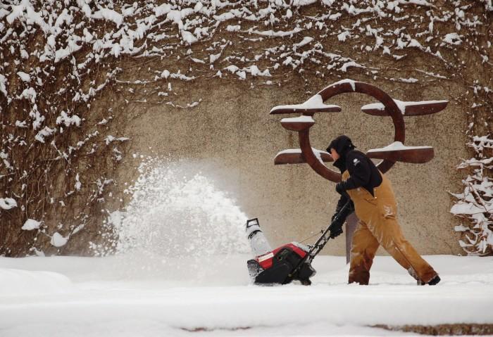 A member of the Smithsonian Garden staff clears snow in the Hirshhorn Sculpture Garden. (Photo courtesy Smithsonian Gardens)