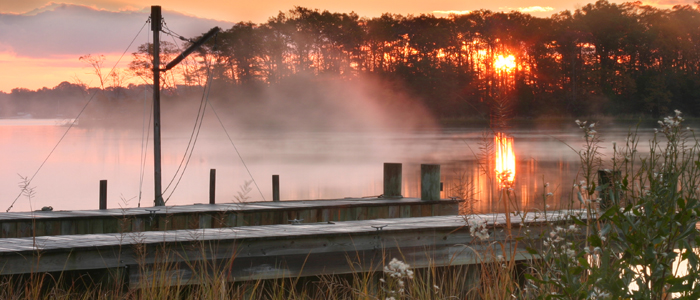 Mist rising on river at sunrise