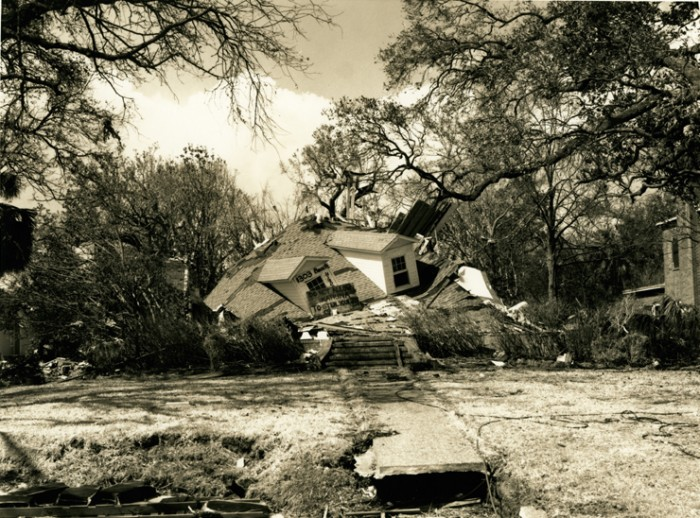 "Smashed House, Katrina, Gulf Coast, Mississippi, 2005. This house, destroyed by Hurrican Katrina, has completely collapsed under its roof, which is still largely intact.  Photograph by Melody Golding, Melody Golding ""Katrina"" Photographic Documentation Project, 2005-2008, Archives Center, National Museum of American History. Gift of the artist."