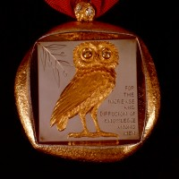 "The Smithsonian's Badge of Office is a thick, irregularly shaped medallion made of 18-carat gold that hangs from a cherry-red ribbon. Cast in high relief and set within a deeply recessed square on the front is the owl of Athena, a symbol of wisdom, and an olive branch, a symbol of peace and goodwill. The owl has forward-gazing eyes that are set with a pair of large, yellow sapphires. To the side of the owl is engraved the Smithsonian Institution's mandate as defined in James Smithson's will: ""For the Increase and Diffusion of Knowledge Among Men."" The back is engraved with the sunburst seal of the Smithsonian and ""James Smithson, 1765—Bicentennial 1965."" (Image courtesy Smithsonian Institution)"