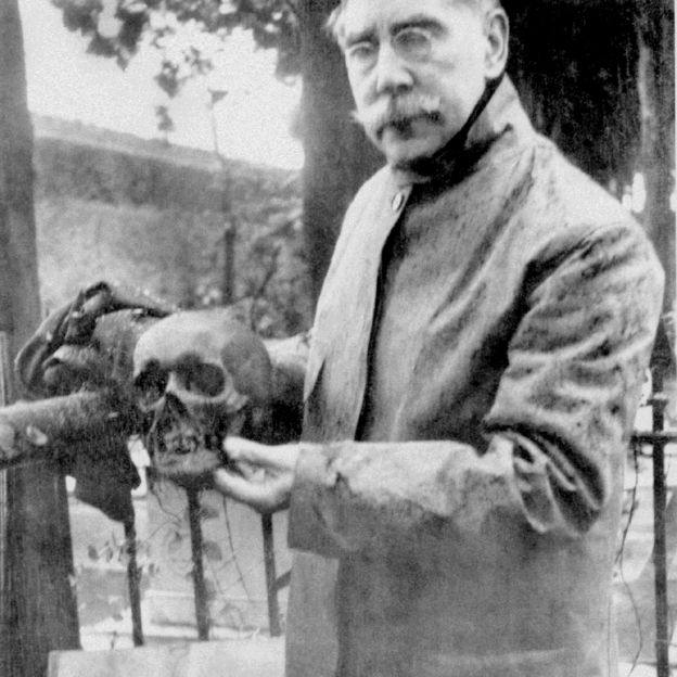 The U.S. Consul to Genoa, William Henry Bishop, holding Smithson's skull during the exhumation of his tomb. (Photo by Mabel Bell, 1904)