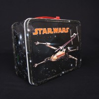 Star Wars Episode IV: A New Hope lunch box from the 1977 film. On this side of the lunch box, a TIE fighter shoots at an X-wing (2001.3101.18.01 and .02)