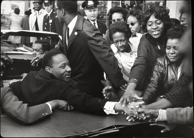 This photograph shows Martin Luther King Jr. (1929–1968) greeting supporters in Baltimore after he won the Nobel Peace Prize in 1964. (Martin Luther King Jr. by Leonard Freed, gelatin silver print, 1964. National Portrait Gallery, Smithsonian Institution)